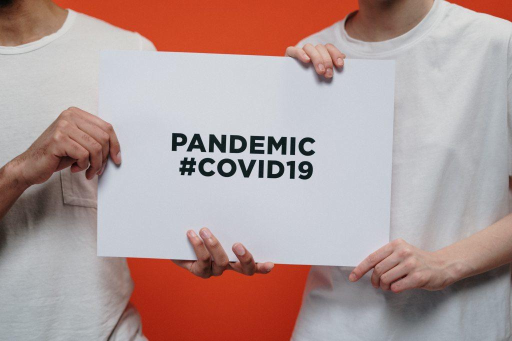 """deux hommes tiennent pancartes """"pandemic #COVID19"""